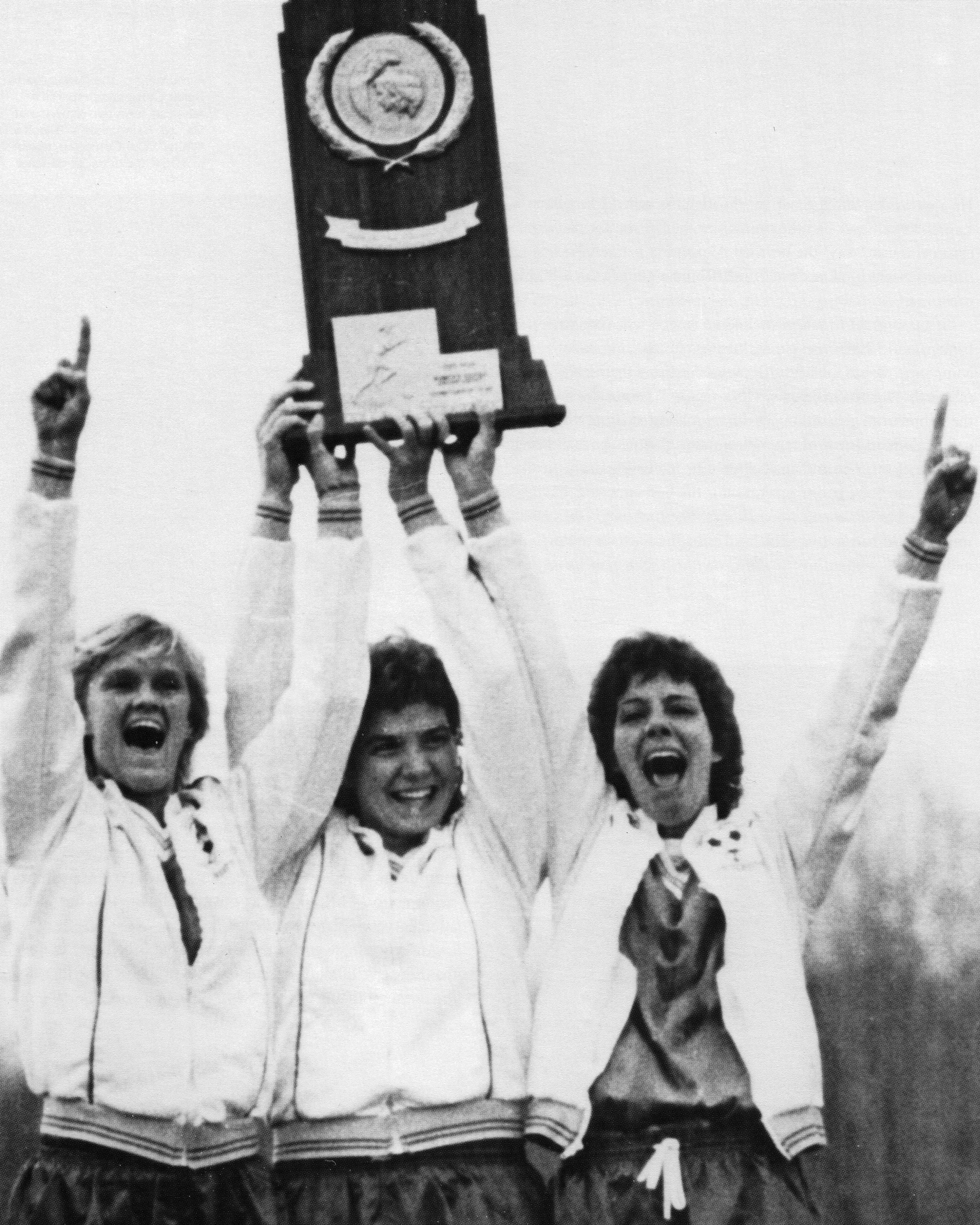 George Mason University Soccer team members (left to right) Sis Koskinen, Pam Baughman, and Meg Romaine lift the NCAA Division I National Championship trophy. Mason Magazine, George Mason University Archives, University Publications, Special Collections Research Center, George Mason University Libraries.