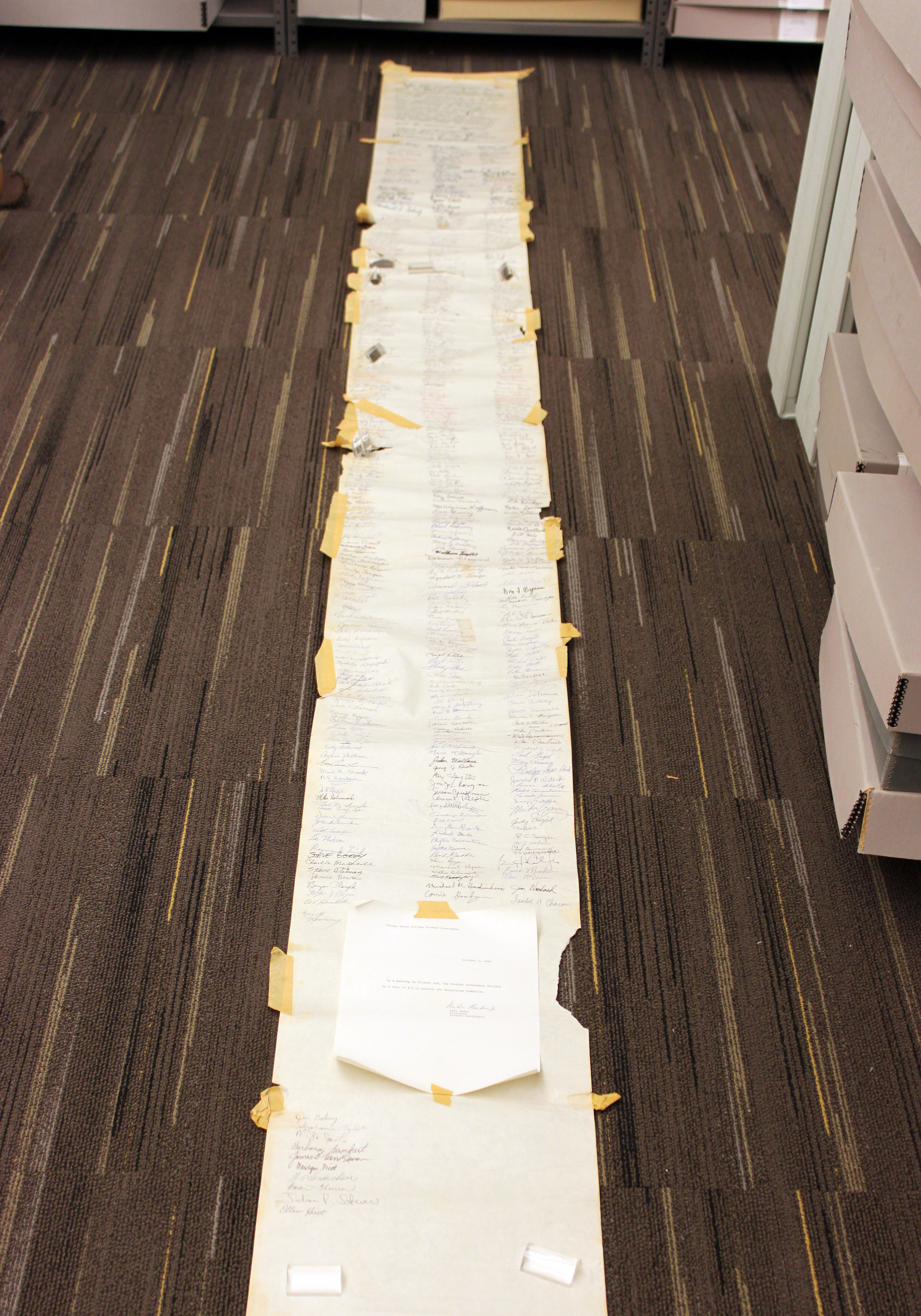 The Vietnam Moratorium Scroll opened up in the SCRC collections storage area. The document is over 12 feet long. From the George Mason University Office of the President records, 1949-2004 #R0019.